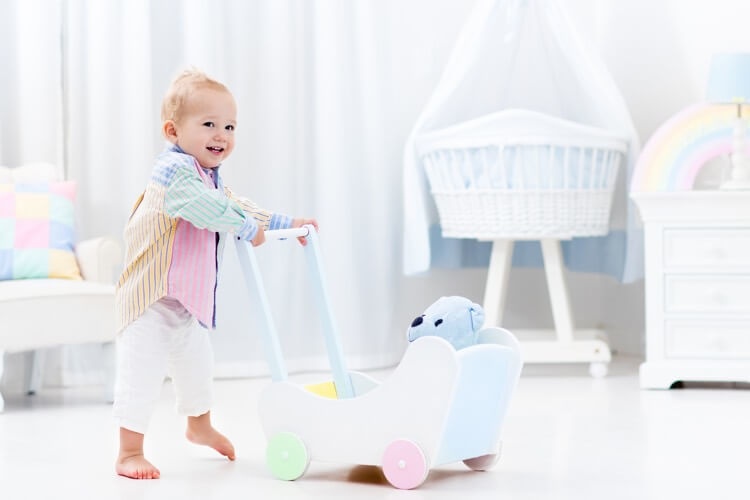 Baby learning to walk with wooden push walker