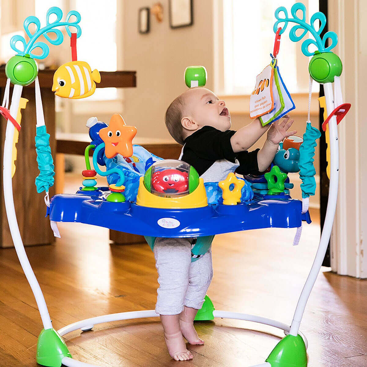 Image of a baby playing in Baby Einstein Jumper in living room.