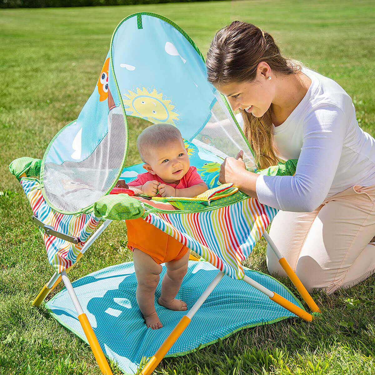 Outdoor image of a baby in Summer Infant Pop Jump Portable Activity Center and her mother looking after her.