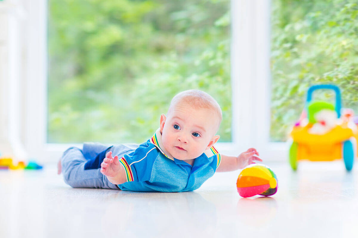 Image of a cute baby on a clean floor with toys during her tummy time.
