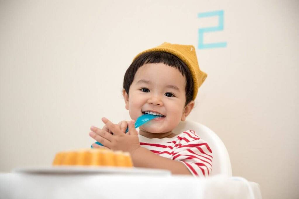 Baby with a cap is eating and smiling in light room
