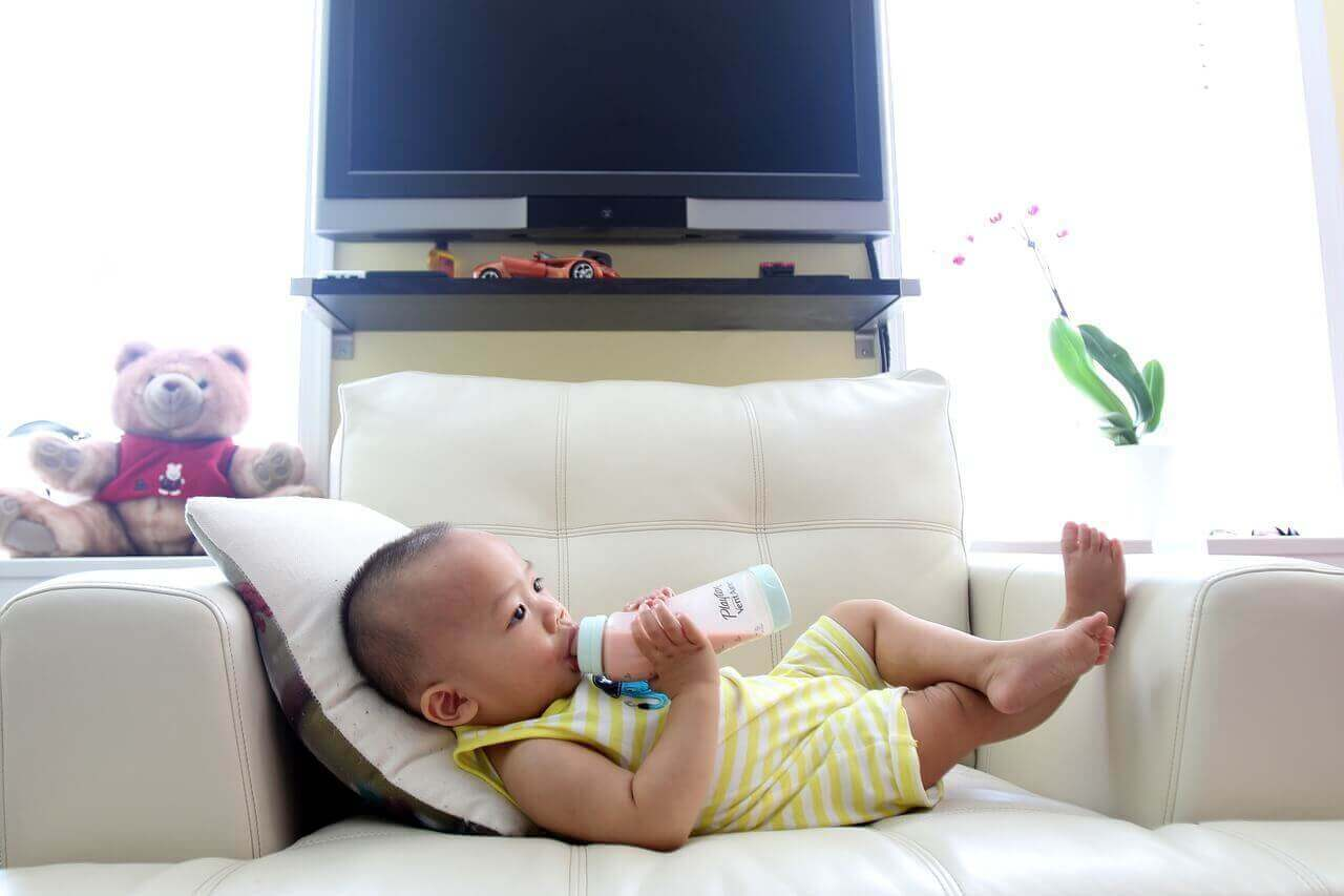Baby is drinking milk in living room in armchair.