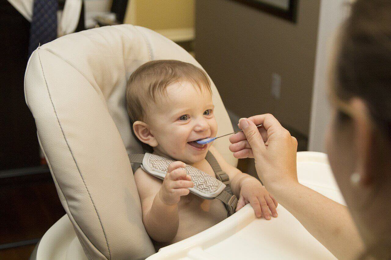 Mother is trying to feed her baby which is in baby chair