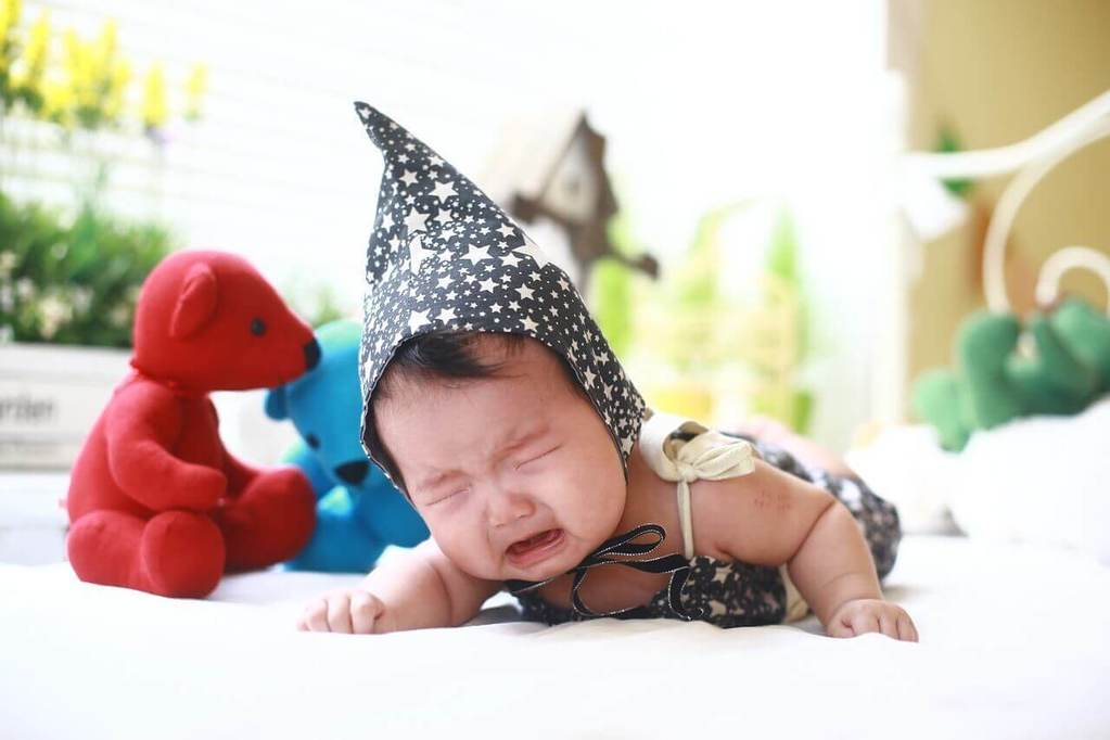 Baby with hat is crying on bed with toys around her