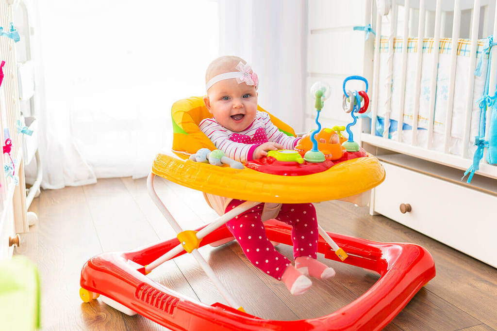 Cute baby girl in a yellow and red coloured walker on a wooden floor.