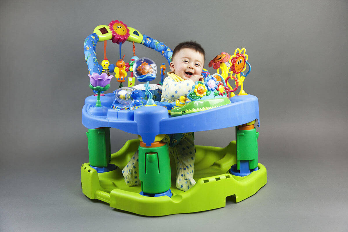 Image of smiling baby boy in the baby activity center on clear black background, photoshoot