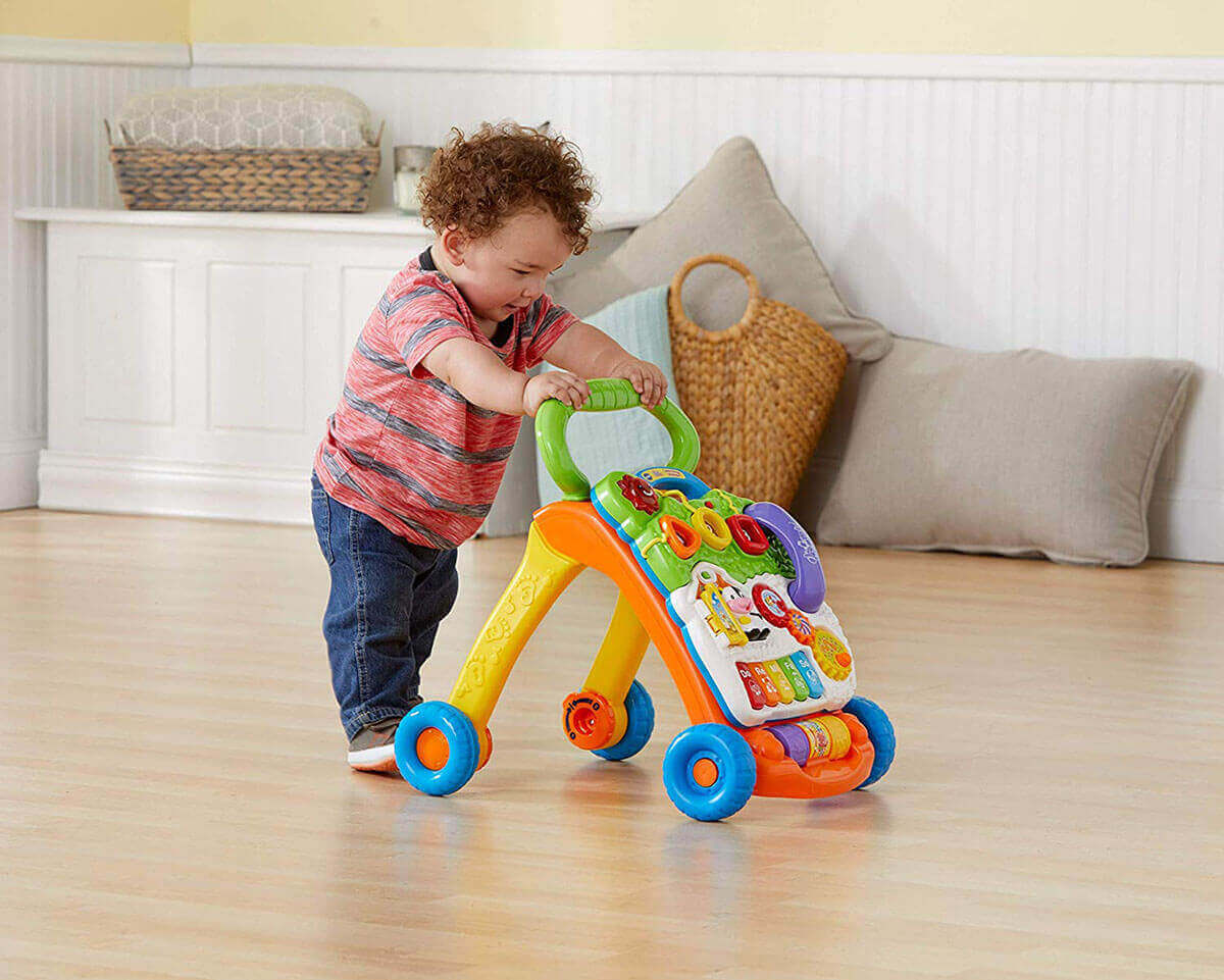 A baby is learning to walk with Vtech learning walker on wooden floor.